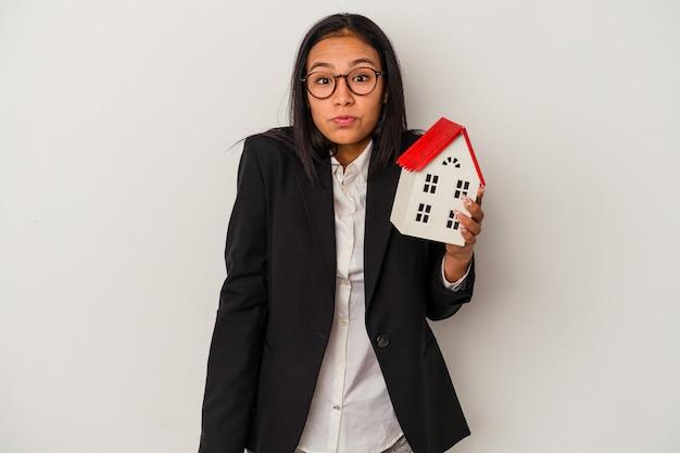 Joven mujer latina de negocios sosteniendo una casa de juguete aislada sobre fondo blanco se encoge de hombros y abre los ojos confundidos.