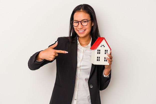 Joven mujer latina de negocios sosteniendo una casa de juguete aislada sobre fondo blanco persona apuntando con la mano a un espacio de copia de camisa, orgulloso y seguro