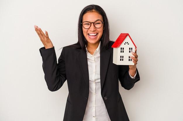 Joven mujer latina de negocios sosteniendo una casa de juguete aislada sobre fondo blanco recibiendo una agradable sorpresa, emocionada y levantando las manos.