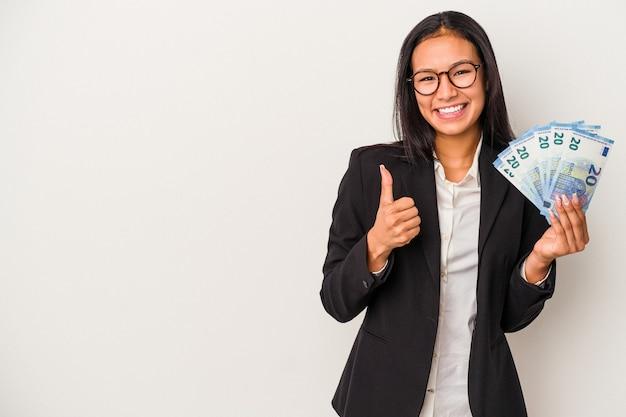 Joven mujer latina de negocios sosteniendo facturas café aislado sobre fondo blanco sonriendo y levantando el pulgar hacia arriba