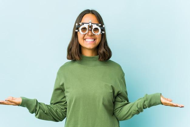 Joven mujer latina oculista hace escala con los brazos, se siente feliz y segura.