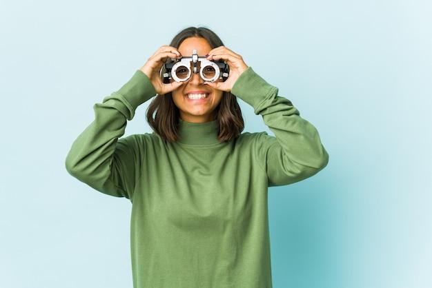 Joven mujer latina oculista mostrando bien firmar sobre los ojos
