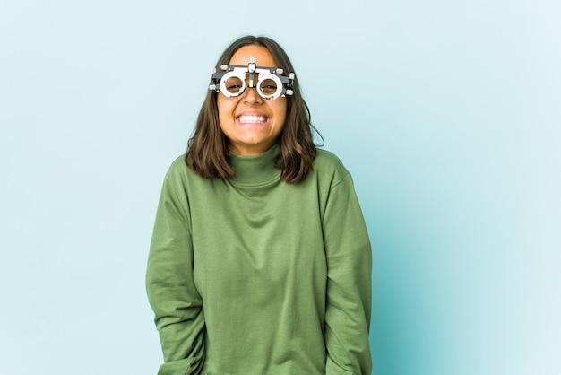 Joven mujer latina oculista sobre pared aislada se ríe y cierra los ojos, se siente relajada y feliz.