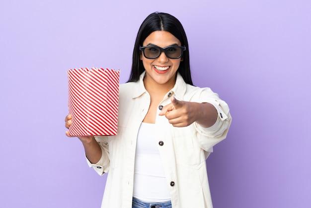Joven mujer latina en la pared blanca con gafas 3d y sosteniendo un gran cubo de palomitas de maíz mientras apunta hacia adelante