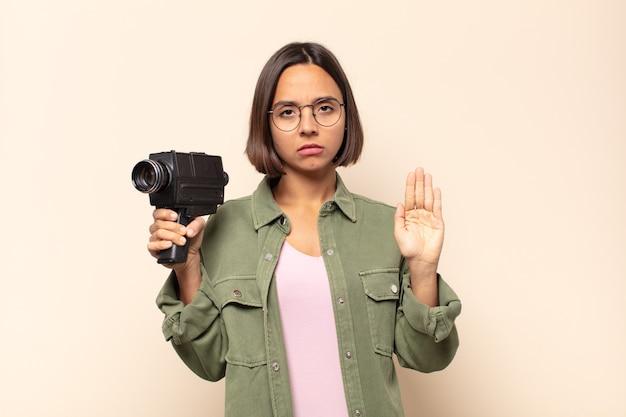 Joven mujer latina que parece seria, severa, disgustada y enojada mostrando la palma abierta haciendo gesto de parada