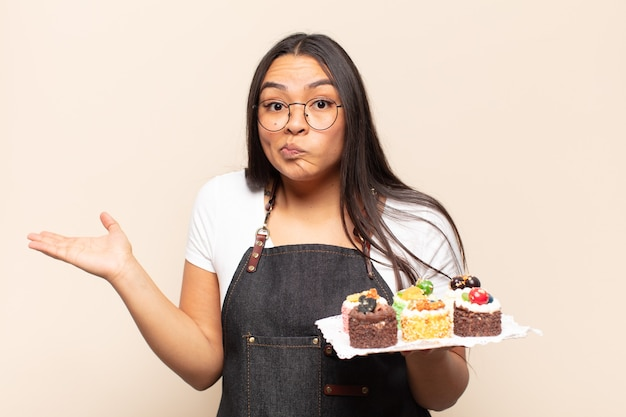 Joven mujer latina que se siente perpleja y confundida, dudando, ponderando o eligiendo diferentes opciones con expresión divertida