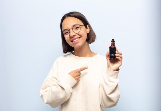 Joven mujer latina sonriendo alegremente, sintiéndose feliz y apuntando hacia un lado y hacia arriba, mostrando el objeto en el espacio de la copia