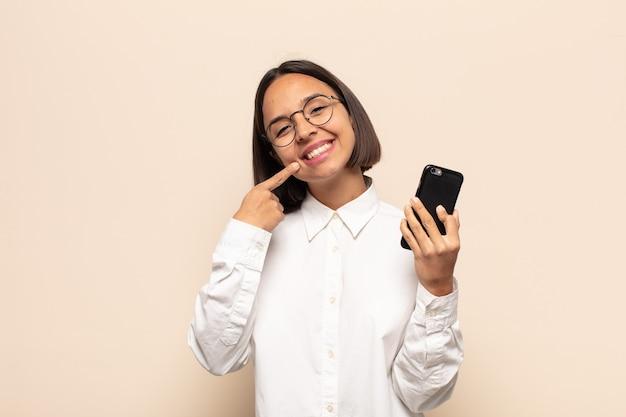 Joven mujer latina sonriendo con confianza apuntando a su propia sonrisa amplia, actitud positiva, relajada y satisfecha