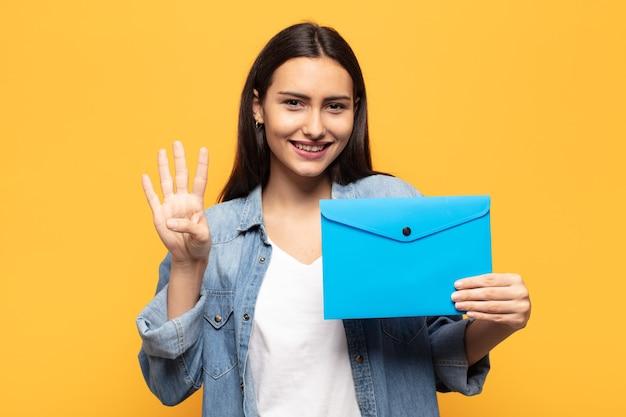 Joven mujer latina sonriendo y mirando amistosamente, mostrando el número cuatro o cuarto con la mano hacia adelante, contando hacia atrás