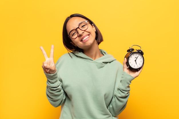 Joven mujer latina sonriendo y mirando amistosamente, mostrando el número dos o el segundo con la mano hacia adelante, contando hacia atrás