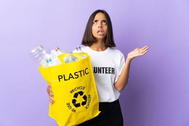 Joven mujer latina sosteniendo una bolsa de reciclaje llena de papel para reciclar aislado en púrpura destacó onwhelmed