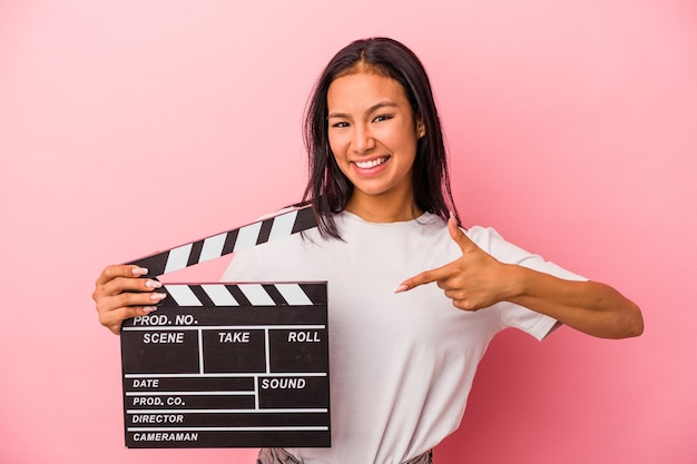 Joven mujer latina sosteniendo claqueta aislada sobre fondo rosa persona apuntando con la mano a un espacio de copia de camisa, orgulloso y seguro