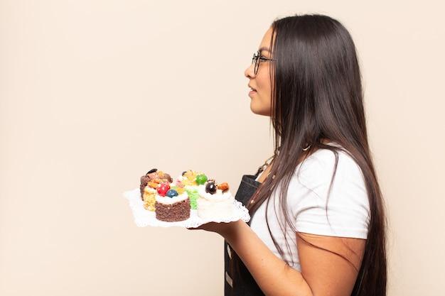 Joven mujer latina en vista de perfil mirando para copiar el espacio por delante, pensando, imaginando o soñando despierto