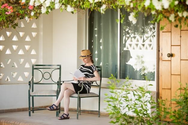 Joven, mujer, lectura, veranda