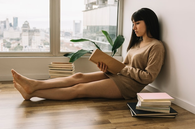 Joven mujer leyendo en el piso