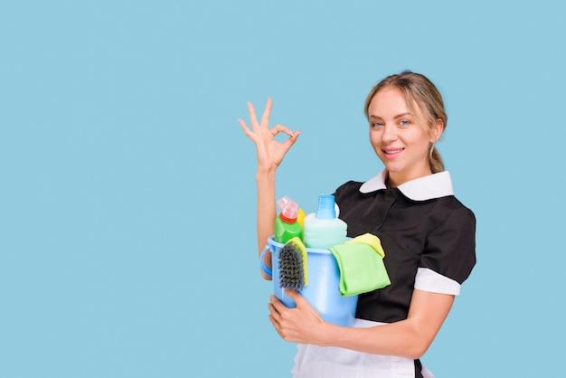 Joven mujer limpiadora feliz mostrando signo bien sosteniendo el cubo de productos de limpieza sobre superficie azul