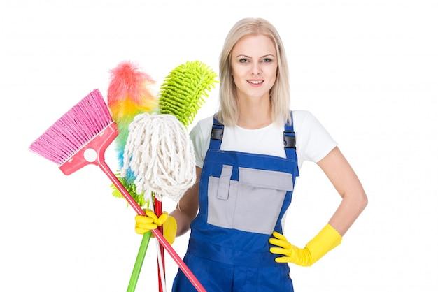 Joven mujer limpiadora sonriente con una escoba.