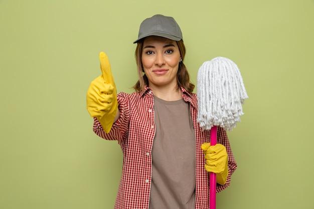 Joven mujer de limpieza en camisa a cuadros y gorra con guantes de goma sosteniendo un trapeador mirando a la cámara sonriendo alegremente mostrando los pulgares para arriba sobre fondo verde