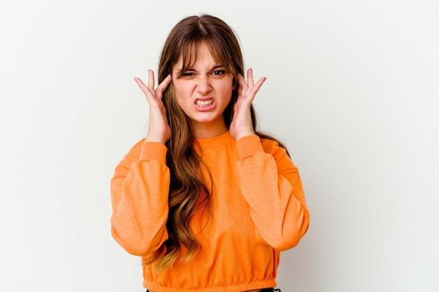 Joven mujer linda caucásica aislada sobre fondo blanco cubriendo las orejas con los dedos, estresada y desesperada por un ambiente ruidoso.