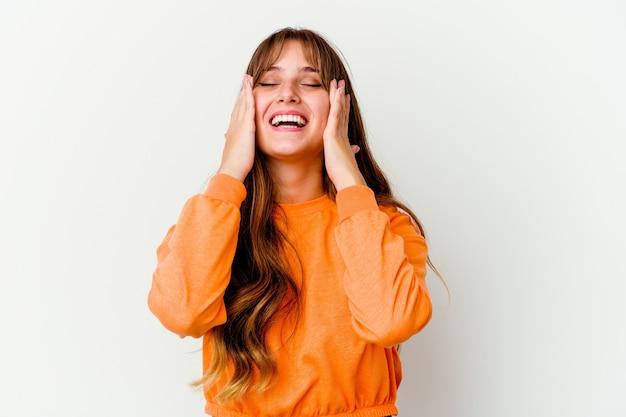 Joven mujer linda caucásica aislada sobre fondo blanco se ríe con alegría manteniendo las manos en la cabeza. concepto de felicidad.