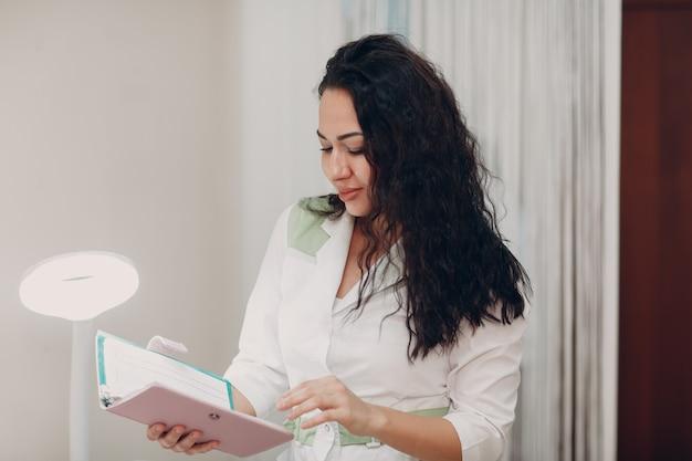 Joven mujer linda enfermera o médico en bata blanca con cuaderno.