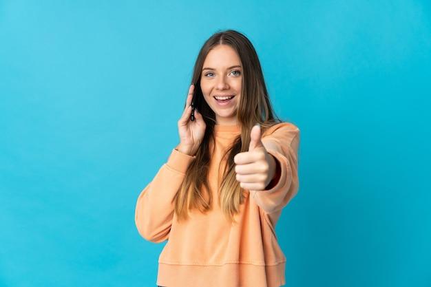 Joven mujer lituana aislada en la pared azul manteniendo una conversación con el móvil mientras hace los pulgares hacia arriba