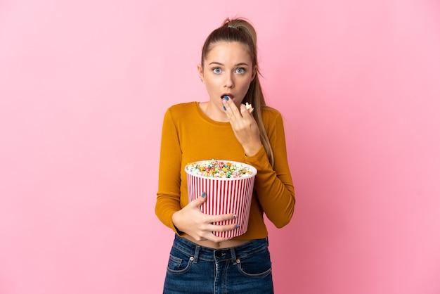 Joven mujer lituana aislada sobre fondo rosa sosteniendo un gran balde de palomitas de maíz