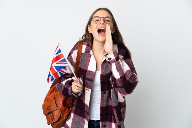 Joven mujer lituana sosteniendo una bandera del reino unido aislado en la pared blanca gritando y anunciando algo