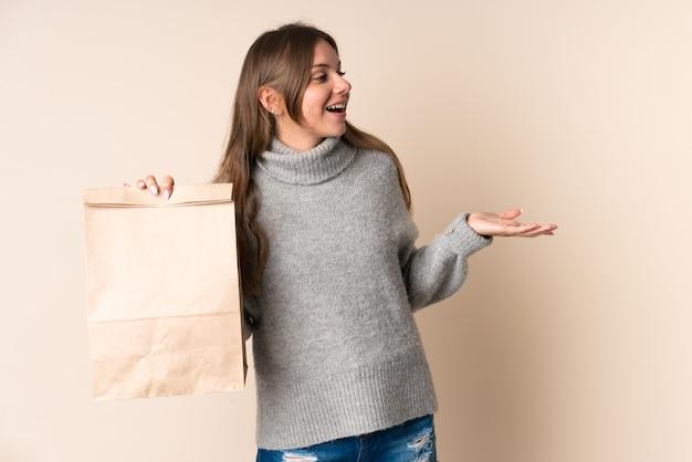 Joven mujer lituana sosteniendo una bolsa de compras con expresión facial sorpresa