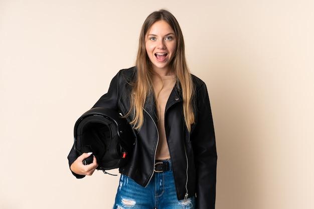 Joven mujer lituana sosteniendo un casco de motocicleta aislado en beige con expresión facial sorpresa