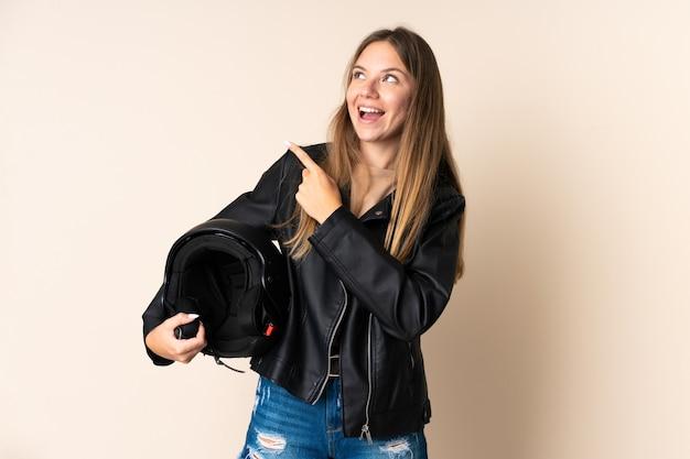 Joven mujer lituana sosteniendo un casco de motocicleta aislado en beige con la intención de darse cuenta de la solución mientras levanta un dedo