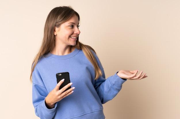 Joven mujer lituana con teléfono móvil aislado en beige con expresión facial sorpresa