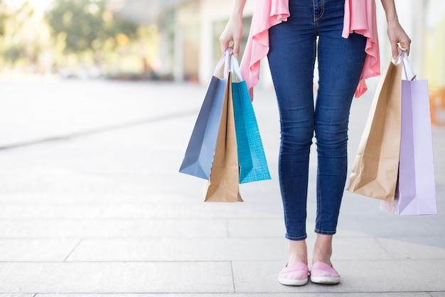 Joven, mujer, llevando, compras, bolsas, calle