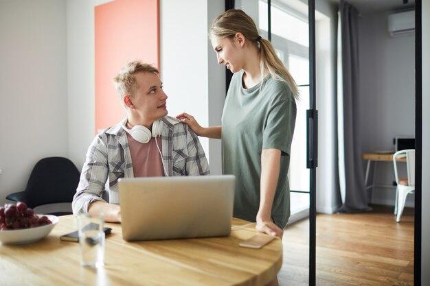 Joven mujer manteniendo su mano sobre el hombro del esposo durante la conversación