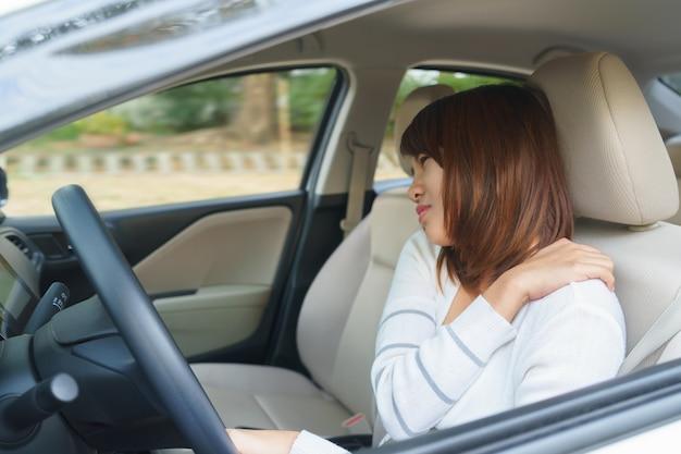 Joven mujer masajeando su brazo u hombro mientras conduce un automóvil después de una hora larga