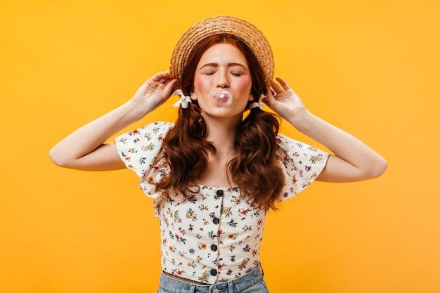 Joven mujer de mejillas rosadas con coleta mastica rumia y se pone sombrero de paja sobre fondo naranja.