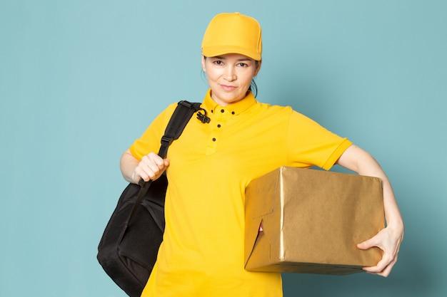 Joven mujer mensajero en camiseta amarilla gorra amarilla con caja en la pared azul