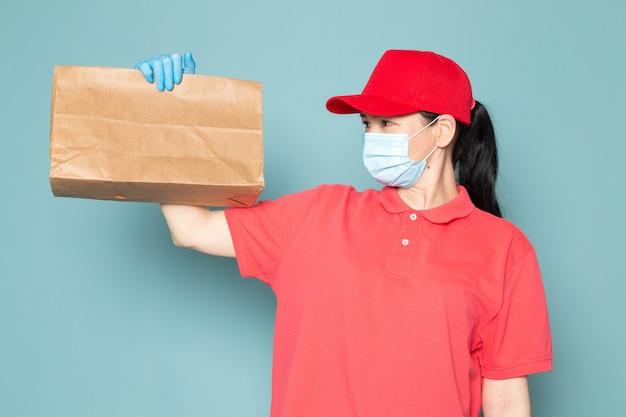Joven mujer mensajero en camiseta rosa gorra roja máscara estéril azul con caja en la pared azul