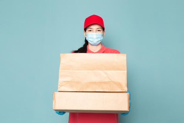 Joven mujer mensajero en camiseta rosada gorra roja máscara azul estéril guantes azules con caja en la pared azul