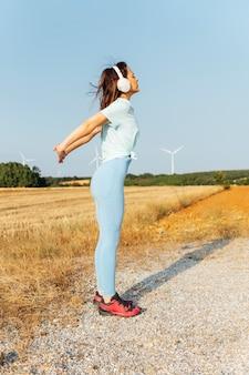 Joven mujer milenaria en cascos y ropa deportiva que se extiende antes de trotar por el campo