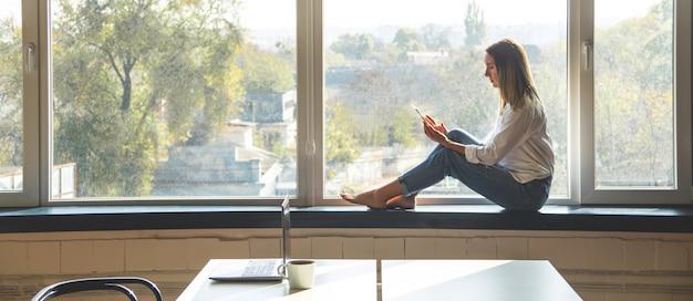 Una joven mujer milenaria mira en un teléfono inteligente mientras está sentado junto a la ventana en un interior luminoso. bandera.