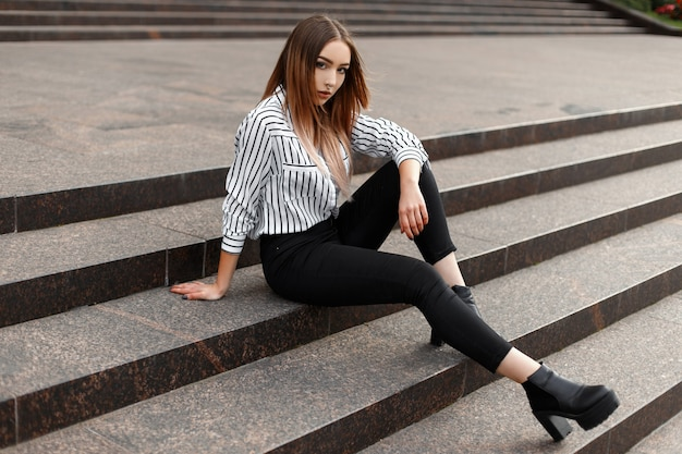 Joven mujer moderna en jeans de moda en una camisa a rayas de moda en zapatos de cuero negro posando en una escalera vintage en la ciudad en un cálido día de primavera al aire libre