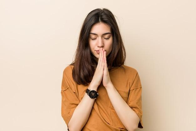 Joven mujer morena contra un fondo beige tomados de la mano en rezar cerca de la boca