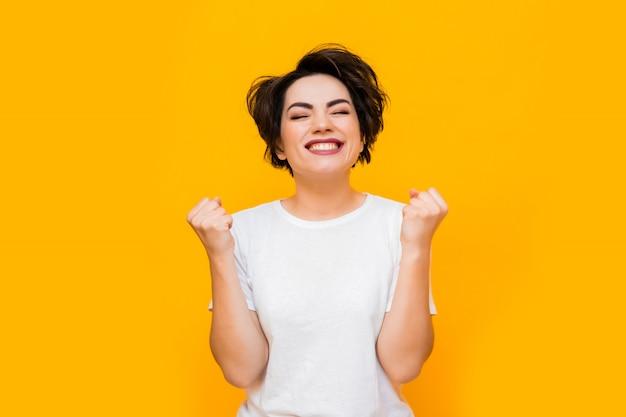 Joven mujer morena feliz con un corte de pelo corto en una camiseta blanca sobre un fondo amarillo. retrato de una mujer joven con diversas emociones sobre un fondo amarillo. espacio para texto