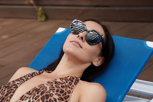 Joven mujer morena con gafas de sol negras se encuentra en la tumbona azul y tomar el sol, hermosa chica con traje de baño con estampado de leopardo relajante en el resort