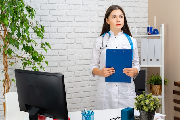 Joven mujer morena médico permanente con portapapeles en su oficina