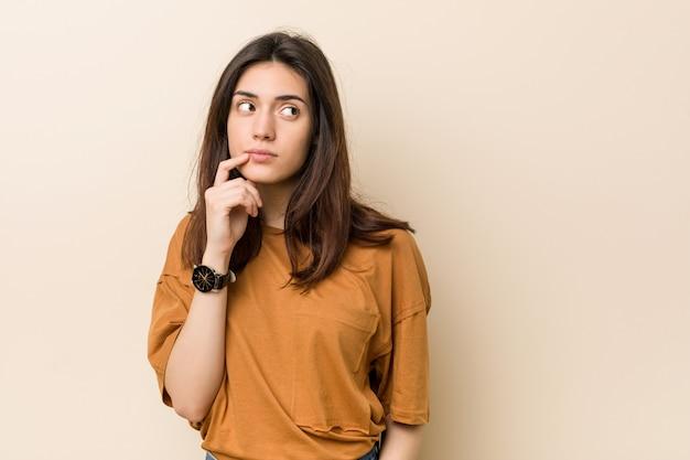 Joven mujer morena mirando hacia los lados con expresión dudosa y escéptica.