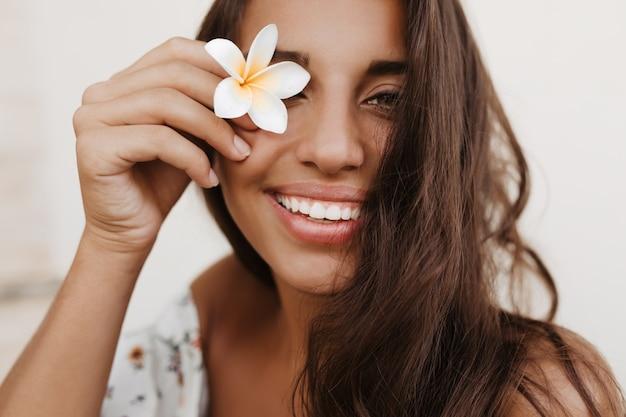 Joven mujer morena rizada cubre sus ojos con flor blanca