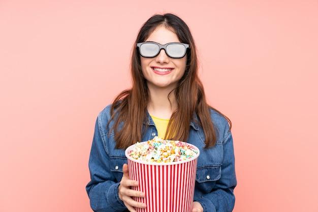 Joven mujer morena rosa con gafas 3d y sosteniendo un gran cubo de palomitas de maíz