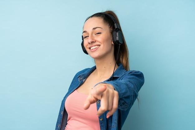 Joven mujer morena sobre pared azul aislada escuchando música y apuntando hacia el frente